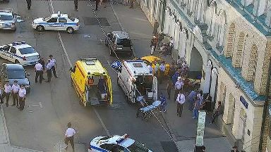 An ambulance and police work at the site of an incident after a taxi crashed into pedestrians in Moscow