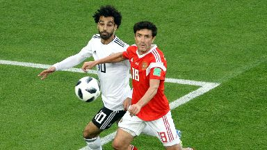 Egypt attacker Mo Salah vies with Russia defender Yuri Zhirkov for the ball.