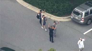 People could be seen leaving the building with their hands up.