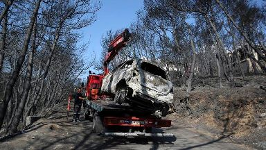 Forensics experts work to identify the dead after Greek fire
