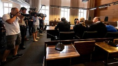 Photographers take pictures of the a man and a woman in the court in Freiburg before sentencing.