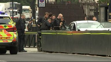 Armed police surround the car in the aftermath of the Parliament crash August 14 2018.