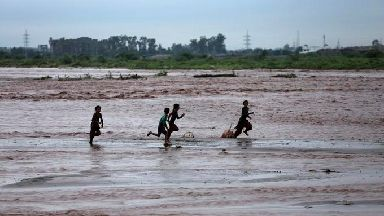 Indian children play in the River Tawi flooded following monsoon rains in Jammu.