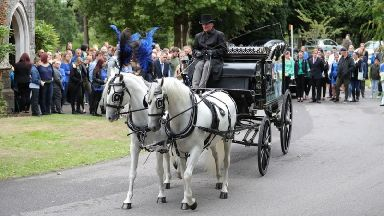 A horse-drawn hearse carries the coffin of 13-year-old Lucy McHugh.
