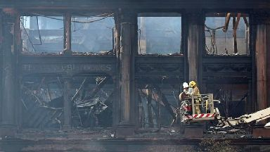 A firefighter and engineers inspecting the charred facade of the Primark store in Belfast.