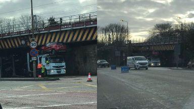 Stuck: Lorry lodged under bridge.