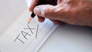 Council Tax Generic image from Unsplash, Tax written down, man holding pencil